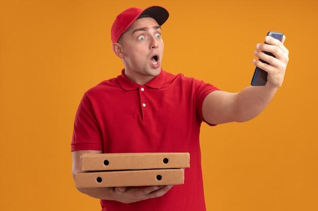 Erschrockener junger lieferbote, der uniform mit kappe hält, die pizzakästen hält, die telefon in seiner hand lokalisiert auf orange wand betrachten