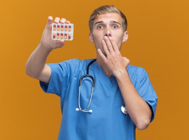 Erschrockener junger männlicher arzt, der arztuniform mit stethoskop hält, das pillen hält, bedeckte mund mit hand lokalisiert auf orange wand