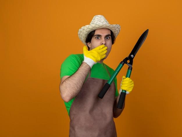 Erschrockener junger männlicher gärtner in der uniform, die gartenhut mit handschuhen hält, die clipper bedeckten mund mit hand bedeckten