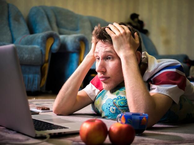 Erschrockener junger mann, der auf dem boden liegt und horrorfilm aufpasst