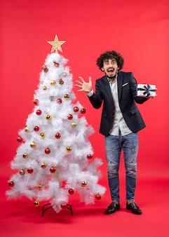 Erschrockener junger mann, der sein geschenk hält, das nahe geschmücktem weißem weihnachtsbaum auf der rechten seite von rot steht