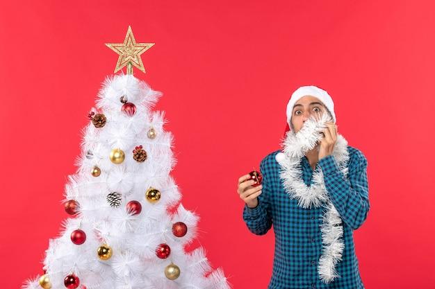 Erschrockener junger mann mit weihnachtsmannhut in einem blau gestreiften hemd und im dekorationszubehör stehend