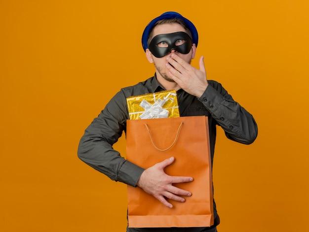 Erschrockener junger party-typ, der blauen hut mit maskerade-augenmaske trägt, die geschenktüte bedeckt mund mit hand lokalisiert auf orange hält