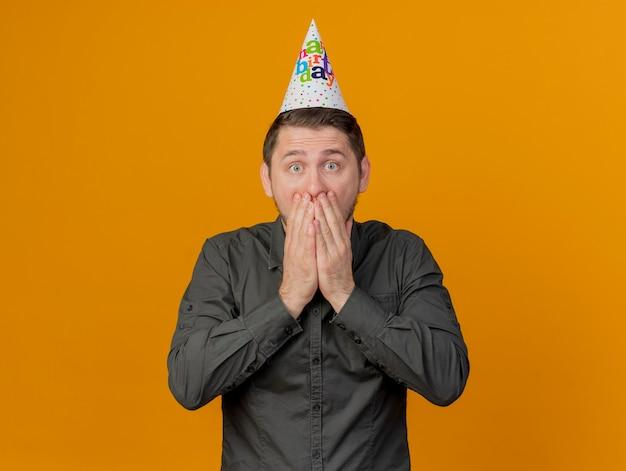 Erschrockener junger party-typ, der geburtstagskappe bedeckt mund mit händen auf orange isoliert trägt