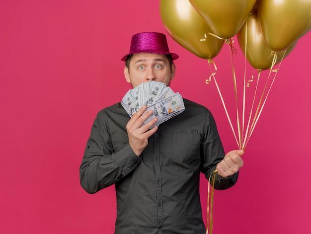 Erschrockener junger party-typ, der rosa hut hält, der ballons bedecktes gesicht mit bargeld lokalisiert auf rosa hält