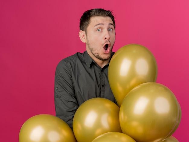 Erschrockener junger party-typ, der schwarzes hemd trägt, das hinter den auf rosa isolierten luftballons steht