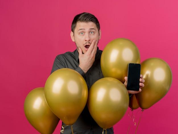 Erschrockener junger party-typ, der schwarzes hemd trägt, das unter luftballons hält telefon hält hand auf mund lokalisiert auf rosa