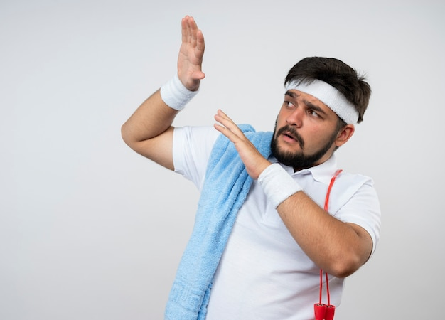 Erschrockener junger sportlicher mann, der seite betrachtet, die stirnband und armband mit handtuch und springseil auf schulter trägt, die hände lokalisiert auf weißer wand hebt