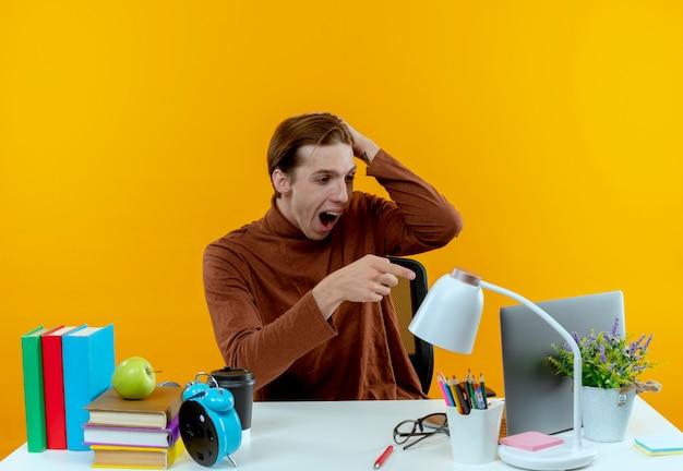 Erschrockener junger studentjunge, der am schreibtisch mit den schulwerkzeugen sitzt und auf laptop zeigt und hand auf kopf auf gelb legt