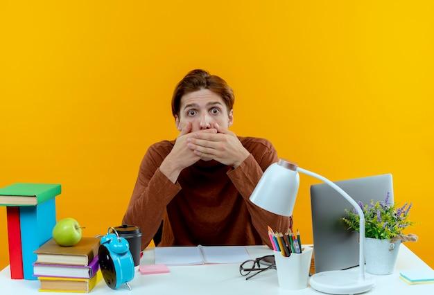 Erschrockener junger studentjunge, der am schreibtisch mit schulwerkzeugen sitzt, bedeckte mund mit hand auf gelb
