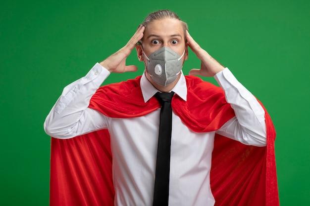 Erschrockener junger superheld kerl, der medizinische maske und krawatte trägt, die hände auf tempel lokalisiert auf grün setzen