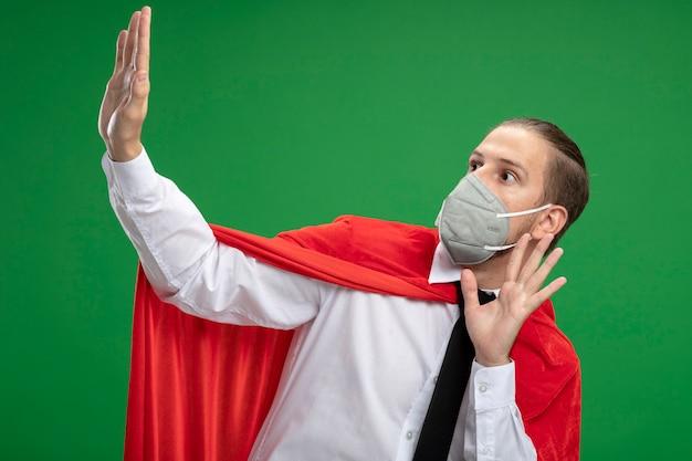 Erschrockener junger superheld kerl, der medizinische maske und krawatte trägt, die seite betrachtet und hände an der kamera lokalisiert auf grünem hintergrund hält