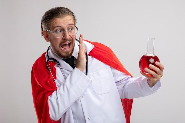 Erschrockener junger superhelden-typ, der medizinische robe mit stethoskop und gläsern trägt, die chemieglasflasche gefüllt mit roter flüssigkeit lokalisiert auf weißem hintergrund halten