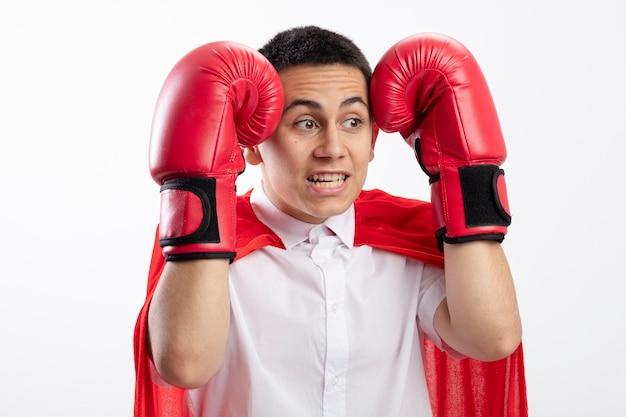 Erschrockener junger superheldenjunge im roten umhang, der kastenhandschuhe trägt, die kopf mit händen berühren, die seite lokalisiert auf weißem hintergrund betrachten