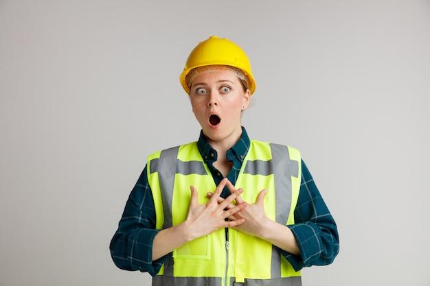 Erschrockener junger weiblicher bauarbeiter, der schutzhelm und sicherheitsweste trägt, die hände auf brust halten, die seite betrachten