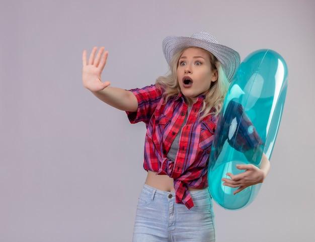 Erschrockener junger weiblicher reisender, der rotes hemd im heu hält aufblasbaren ring, der stoppgeste auf isolierter weißer wand zeigt