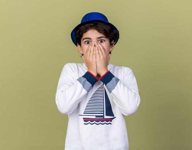 Erschrockener kleiner junge mit blauem partyhut bedecktes gesicht mit händen isoliert auf olivgrüner wand