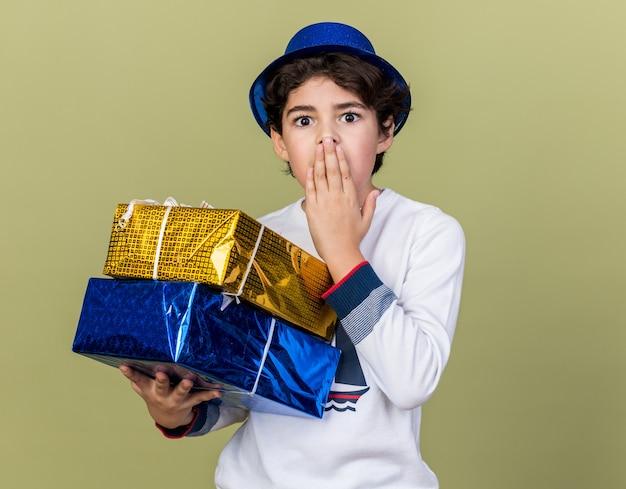 Erschrockener kleiner junge mit blauem partyhut, der geschenkboxen hält, bedeckte den mund mit der hand