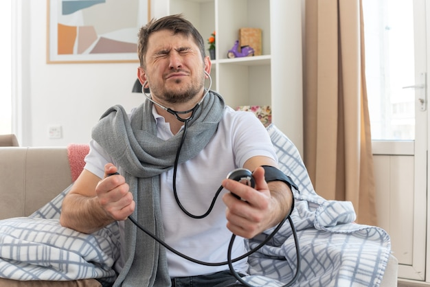 Erschrockener kranker slawischer mann mit schal um den hals, der seinen druck mit einem blutdruckmessgerät misst, das mit geschlossenen augen auf der couch im wohnzimmer sitzt