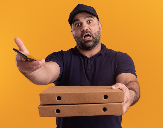 Erschrockener lieferbote mittleren alters in uniform und mütze, die pizzaschachteln mit telefon vorne lokalisiert auf gelber wand heraushalten