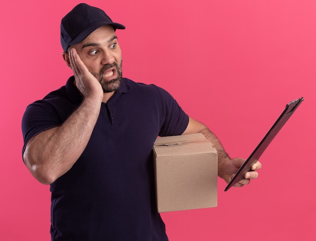 Erschrockener liefermann mittleren alters in uniform und mütze mit box, der die zwischenablage in seiner hand isoliert auf rosa wand betrachtet