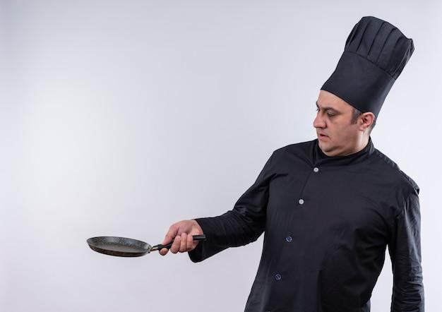 Erschrockener männlicher koch mittleren alters in kochuniform, der die pfanne mit dem kopierraum zur seite hält
