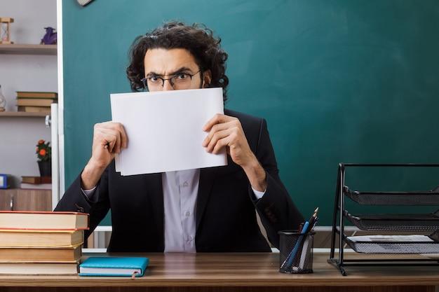 Erschrockener männlicher lehrer, der eine brille trägt und das gesicht mit papier bedeckt, das am tisch mit schulwerkzeugen im klassenzimmer sitzt