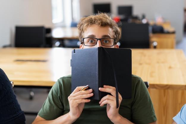 Erschrockener männlicher student, der hinter notizbuch sich versteckt