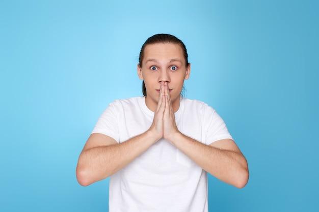 Erschrockener mann im t-shirt auf blauem hintergrund isoliert.