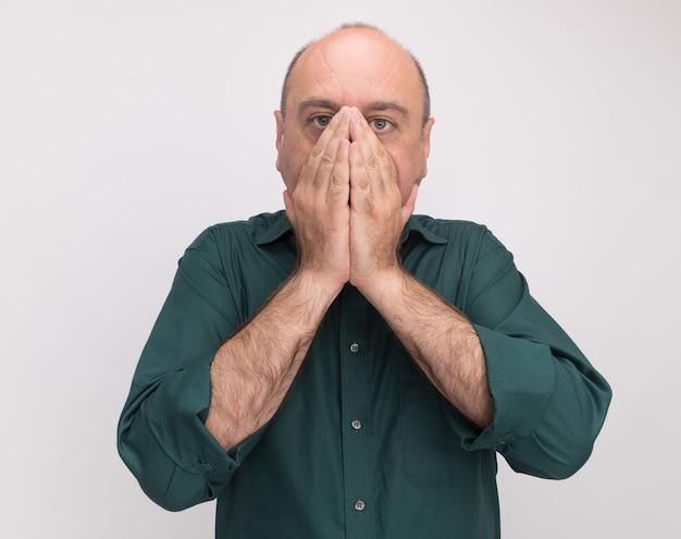 Erschrockener mann mittleren alters, der grünes t-shirt bedecktes gesicht mit auf weißer wand lokalisierten händen trägt