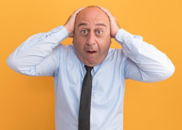 Erschrockener mann mittleren alters, der weißes t-shirt mit krawatte trägt, packte den kopf isoliert auf orange wand