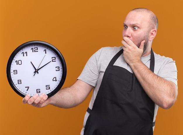 Erschrockener slawischer männlicher friseur mittleren alters in uniform, die wanduhr lokalisiert auf orange wand hält und betrachtet