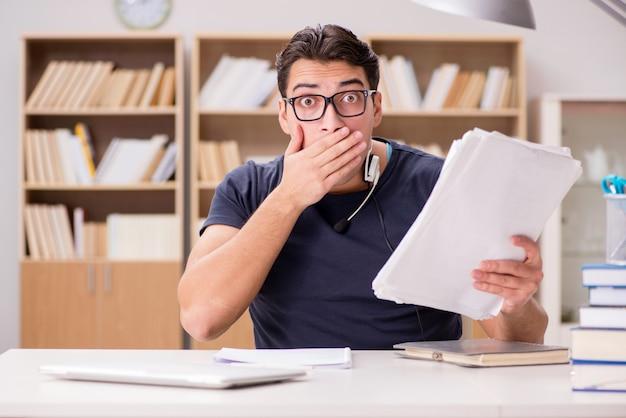 Erschrockener student mit schreibarbeit in der bibliothek
