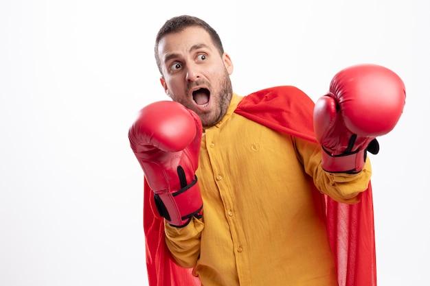 Erschrockener superheld mann steht mit boxhandschuhen isoliert auf weißer wand