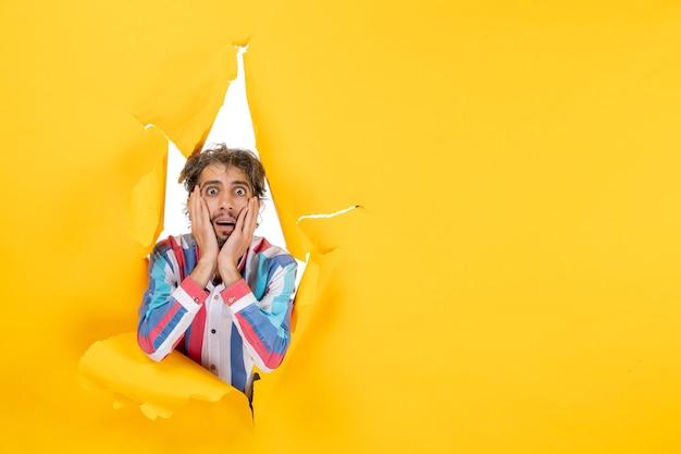 Erschrockener und emotionaler junger mann posiert im zerrissenen gelben papierlochhintergrund