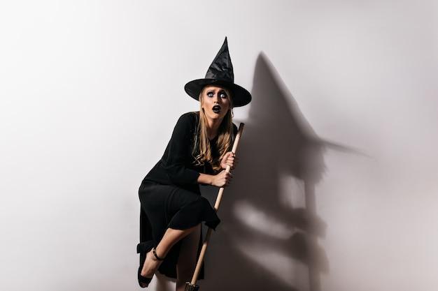 Erschrockener weiblicher zauberer, der magischen besen hält. innenfoto der verängstigten frau im hexenkostüm, das in halloween aufwirft.