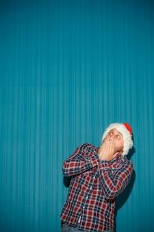 Erschrockener weihnachtsmann, der eine weihnachtsmütze trägt