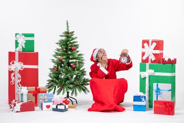 Erschrockener weihnachtsmann in tiefen gedanken, die auf dem boden sitzen und uhr nahe geschenken und geschmücktem weihnachtsbaum auf weißem hintergrund zeigen