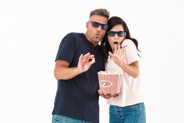 Erschrockenes attraktives paar in lässigem outfit, das isoliert über weißer wand steht und einen film mit popcorn und 3d-brille sieht