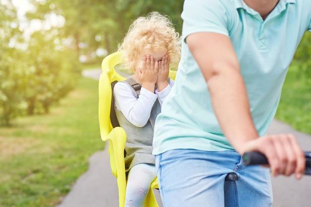 Erschrockenes baby in einem fahrradsitz auf einem fahrrad