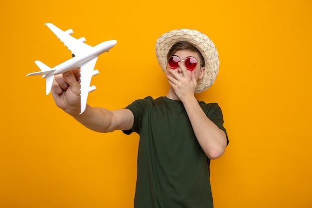 Erschrockenes bedecktes gesicht mit der hand junger gutaussehender kerl, der hut mit brille trägt, die spielzeugflugzeug hält