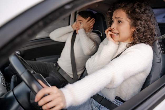 Erschrockenes europäisches paar im persönlichen auto bei unfall junge schöne lockige frau und erwachsener mann ist schockiert. moderne frau als fahrerin. konzept des autofahrens