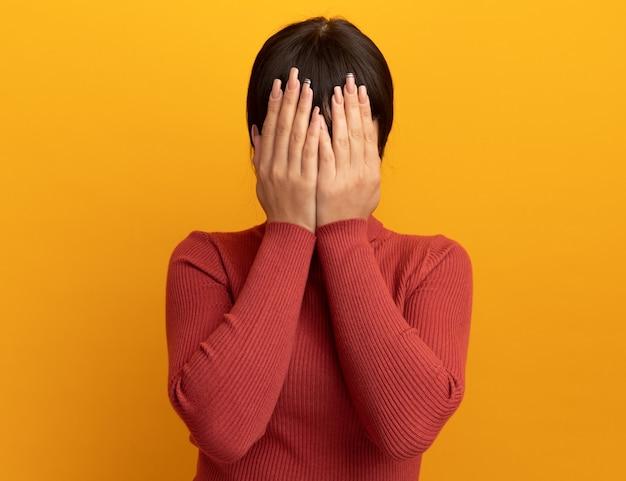 Erschrockenes junges brünettes kaukasisches mädchen bedeckt das gesicht mit den händen, die auf oranger wand mit kopienraum isoliert sind