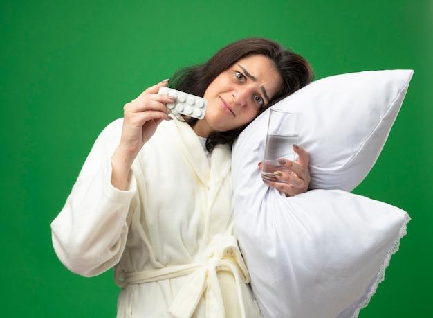 Erschrockenes junges kaukasisches krankes mädchen, das das gewand umarmt, das kissen setzt, das den kopf auf ihn hält, der glas wasser hält und packung der medizinischen tabletten zeigt kamera betrachtet auf lokalem grünem hintergrund