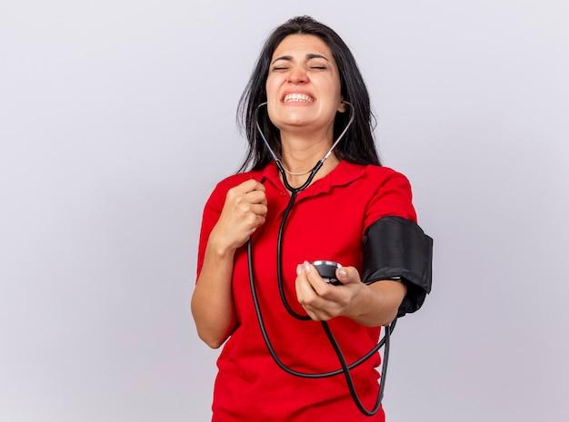 Erschrockenes junges kaukasisches krankes mädchen, das stethoskop trägt, das ihren druck mit blutdruckmessgerät mit geschlossenen augen misst, lokalisiert auf weißem hintergrund mit kopienraum