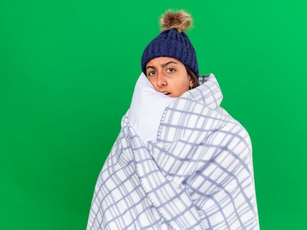 Erschrockenes junges krankes mädchen, das kamera betrachtet, die wintermütze mit schal wickelt, der im karierten umarmenden kissen lokalisiert auf grünem hintergrund umwickelt wird