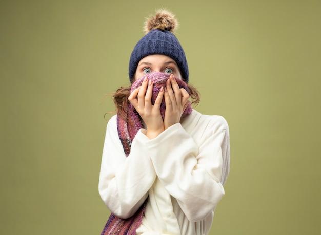 Erschrockenes junges krankes mädchen, das weißes gewand und wintermütze mit schal bedecktes gesicht mit schal trägt