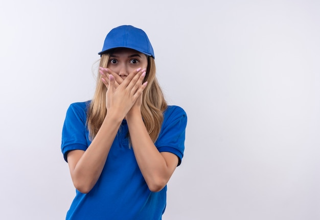Erschrockenes junges liefermädchen, das blaue uniform und bedeckten mund der kappe mit den auf weiß lokalisierten händen trägt