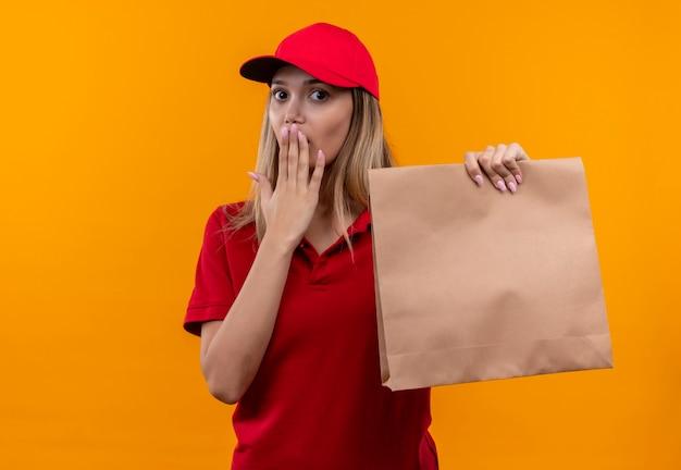 Erschrockenes junges liefermädchen, das rote uniform und kappe hält papiertüte und bedeckten mund lokalisiert auf orange wand