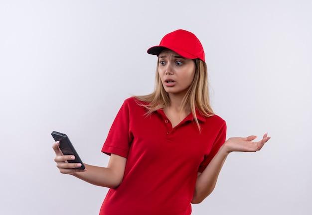 Erschrockenes junges liefermädchen, das rote uniform und mütze hält und telefon lokalisiert auf weiß hält